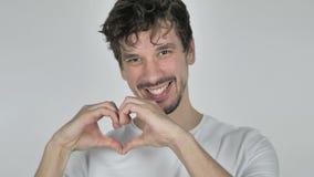 Coeur fait main par le jeune homme occasionnel dans l'amour regardant la caméra clips vidéos