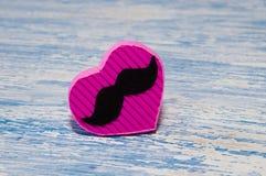 Coeur fait main rose fait de carton sur un fond bleu en bois de vintage Photographie stock