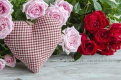 Coeur fait main vérifié contre des roses rouges et roses Photos libres de droits