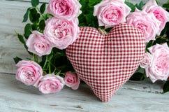 Coeur fait main vérifié contre des roses rouges et roses Image stock