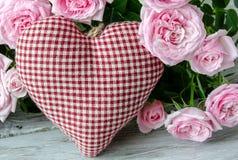 Coeur fait main vérifié contre des roses rouges et roses Photos stock