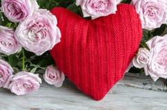 Coeur fait main vérifié contre des roses rouges et roses Photo stock
