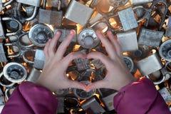 Coeur fait par des mains du ` s d'enfant sur le fond de lumière de casier Images stock