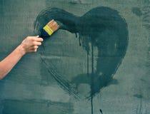 Coeur femelle de peinture de main sur le mur Image libre de droits