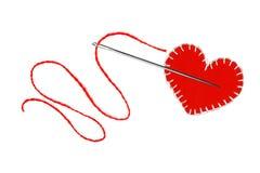 Coeur, fil rouge et aiguille d'isolement sur le blanc Images libres de droits