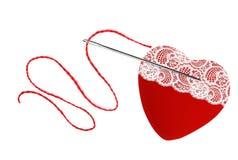 Coeur, fil rouge et aiguille d'isolement sur le blanc Images stock