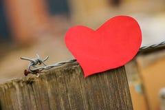 Coeur formé avec le fil en métal et le poteau en bois à l'arrière-plan Photos stock