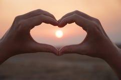Coeur formé par main contre un beau coucher du soleil Photos libres de droits