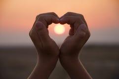 Coeur formé par main contre un beau coucher du soleil Photographie stock libre de droits