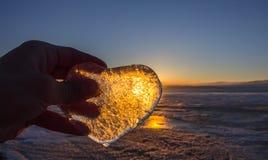Coeur glacial dans sa main à la lumière de coucher du soleil Lac Baikal Images libres de droits