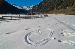 Coeur gravé à l'eau-forte dans la neige avec des montagnes à l'arrière-plan Image libre de droits