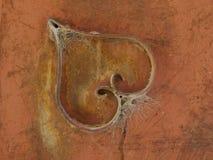 Coeur inversé en métal, cobwebbed sur un mur en pierre orange lumineux, symbole de l'amour, un symbole de jour du ` s de Valentin Photographie stock libre de droits