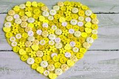 Coeur jaune couvert de boutons colorés Photographie stock