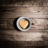 Coeur jaune en céramique dans la tasse de café Photo libre de droits