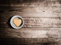 Coeur jaune en céramique dans la tasse de café Image stock