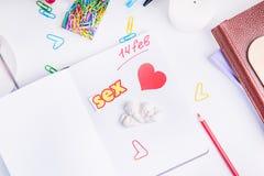 Coeur, lettrage de mot de sexe et stauette rouges d'anges sur l'organisateur personnel sur le lieu de travail Concept de planific Images libres de droits