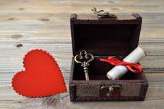 Coeur, lettre d'amour et clé dans le coffre au trésor en bois Image libre de droits