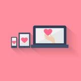 Coeur montré sur l'électronique trois, sur le rose Photos stock