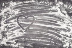 Coeur peint avec le doigt dans le repas de blé sur une surface de fonctionnement grise Photographie stock