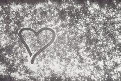 Coeur peint avec le doigt dans le repas de blé sur une surface de fonctionnement grise Image stock