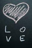 Coeur peint par blanc sur un fond noir Photos libres de droits