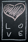 Coeur peint par blanc sur un fond noir Images stock