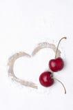 Coeur peint sur le contexte du sucre en poudre et de deux cerises Images stock