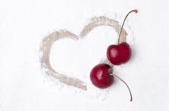 Coeur peint sur le contexte du sucre en poudre et de deux cerises Image libre de droits