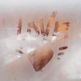 Coeur peint sur une fenêtre misted Pluie d'automne, inscription sur le verre en sueur - amour et coeur Photographie stock