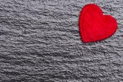 Coeur pelucheux rouge au-dessus de fond noir d'ardoise Photos libres de droits