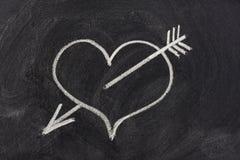 Coeur percé par la flèche, symbole d'amour sur le tableau noir Photos stock