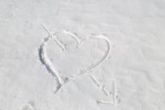 coeur percé par une flèche dans la neige Images libres de droits