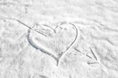 coeur percé par une flèche dans la neige Images stock