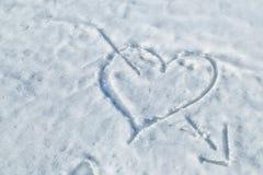 coeur percé par une flèche dans la neige Photo libre de droits