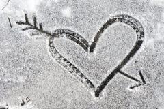 Coeur percé par une flèche dessinée avec la neige Photographie stock