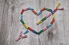 Coeur percé par une flèche faite de pinces à linge en bois Photos libres de droits