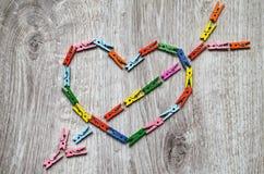 Coeur percé par une flèche faite de pinces à linge en bois Images stock