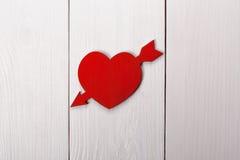 Coeur percé par une flèche sur une table Le jour de Valentine Image libre de droits