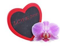 Coeur, plaque en bois au coeur de forme et orchidées, jour du ` s de Valentine Image stock