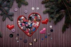 Coeur pour des valentines composées de boutons sur le conseil foncé Photo stock