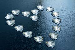 Coeur présenté de l'petits coeurs en cristal sur un fond bleu Photo stock
