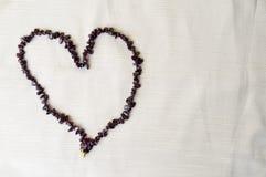 Coeur présenté des belles perles femelles, colliers des pierres foncées brunes, ambres sur un fond de tissu beige Photo stock