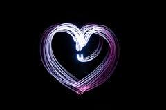 Coeur produit par la lumière au-dessus du fond noir Photographie stock
