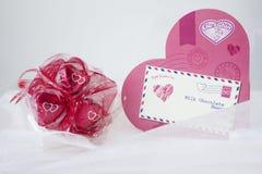 Coeur rose avec un groupe de chocolats enveloppés en papier rouge Images stock