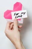 Coeur rose d'origami dans la main du ` s des hommes Photos stock