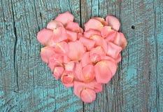 Coeur rose de pétale de rose sur le bois rustique Photographie stock
