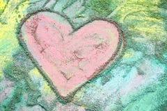 Coeur rose dessiné dans la craie sur le fond coloré d'arc-en-ciel Photos stock