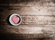 Coeur rose en céramique dans la tasse de café Photos stock
