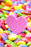 Coeur rose et smarties colorés de chocolat Photo stock