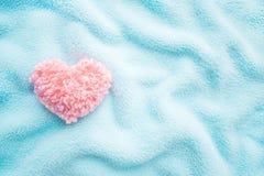 Coeur rose pelucheux de fil sur le fond confortable mou bleu de tissu Ha photographie stock